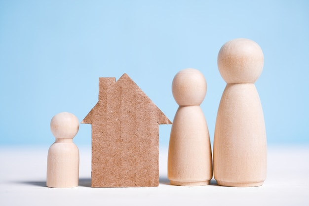 Abstract cardboard house near the family: mom, dad, baby. home ownership . Premium Photo