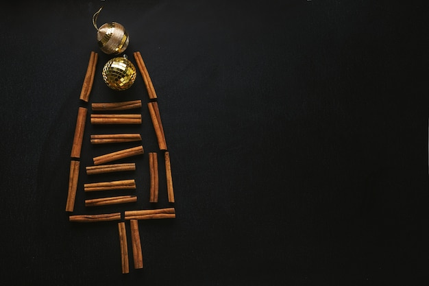 Абстрактная рождественская елка с палочками корицы и снежинками на темном фоне. рождественское понятие Premium Фотографии