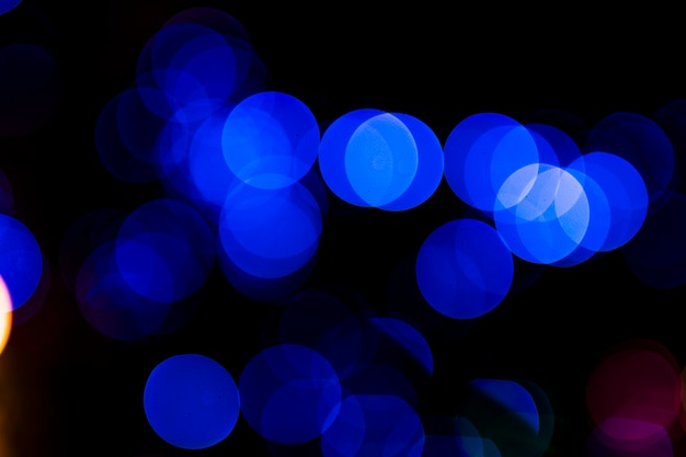 Abstract circular blue light blurred bokeh on dark background Free Photo