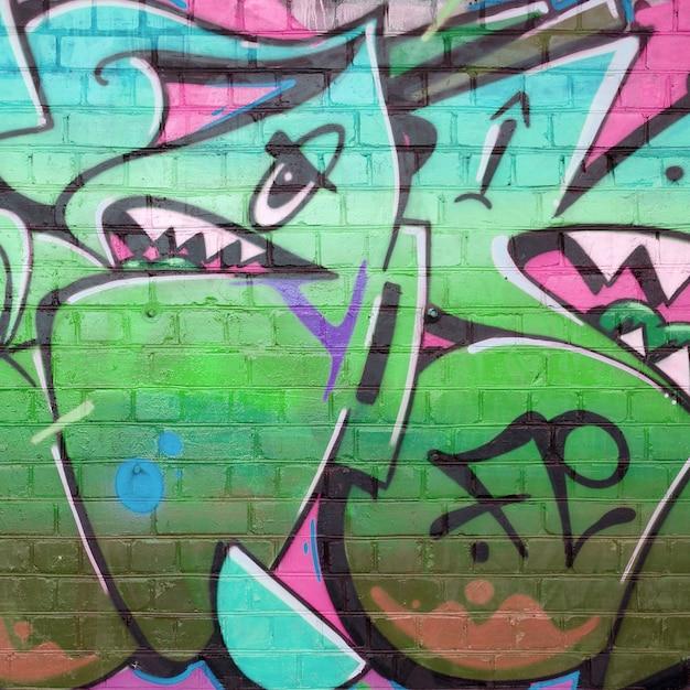 녹색 색상의 오래 된 벽돌 벽에 낙서 그림의 추상 화려한 조각 프리미엄 사진