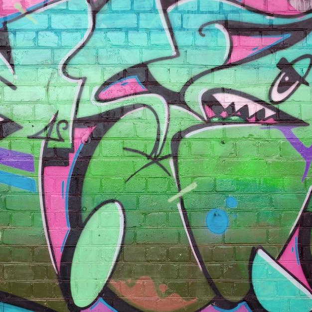 분홍색과 녹색 색상의 오래 된 벽돌 벽에 낙서 그림의 추상 화려한 조각 프리미엄 사진
