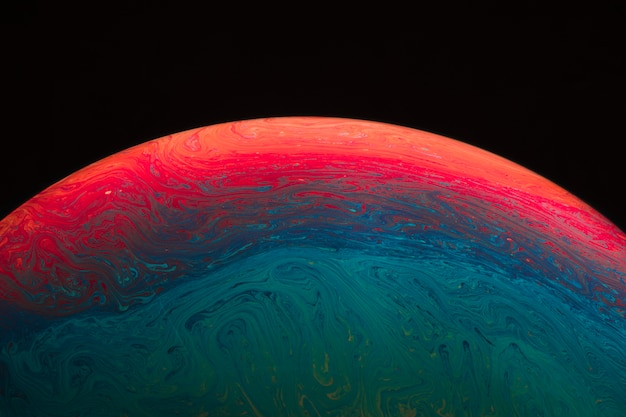 Abstract colorful hued vivid soap bubble on black background Free Photo