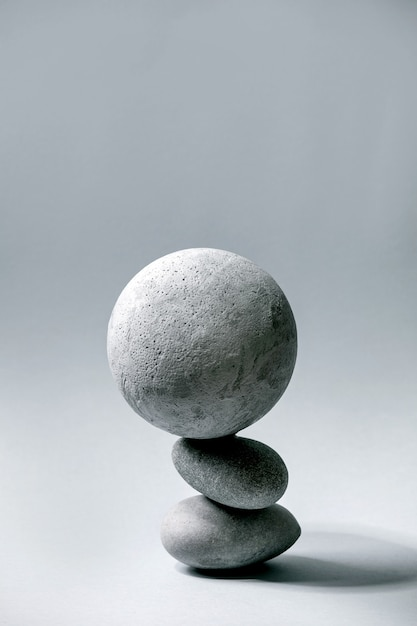 Abstract  composition of balanced grey geometric objects sphere and stones. copy space. modern concept for product presentation. Premium Photo