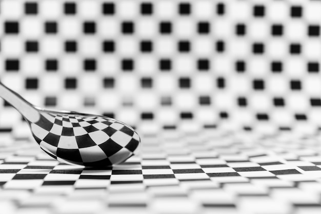 Abstract geometric black and white or checkered marble with a reflection of a spoon for background Premium Photo