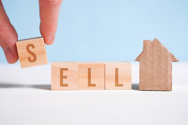Abstract house made of cardboard hand holds with wooden cubes with the word sell. home sale . Premium Photo
