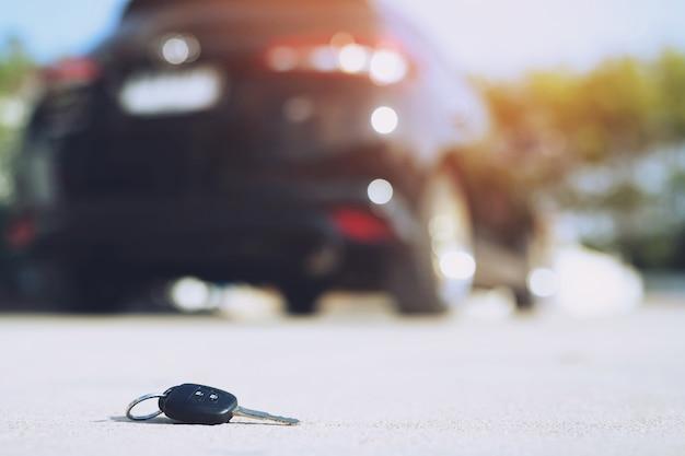 抽象的な失われた車の鍵は、通りのコンクリートセメント地面道路の家の前庭に横たわって落ちる。 Premium写真