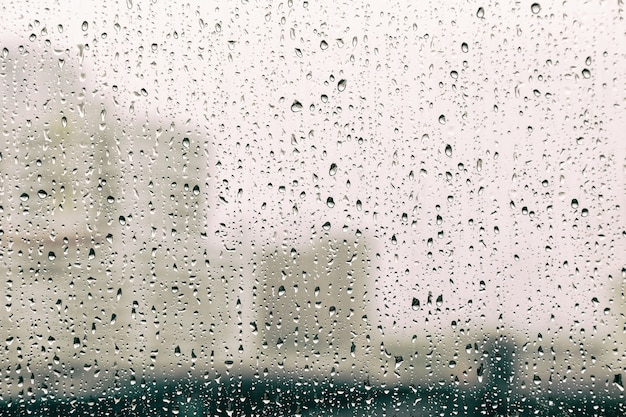 abstract rain droplets on window glass while raining photo premium
