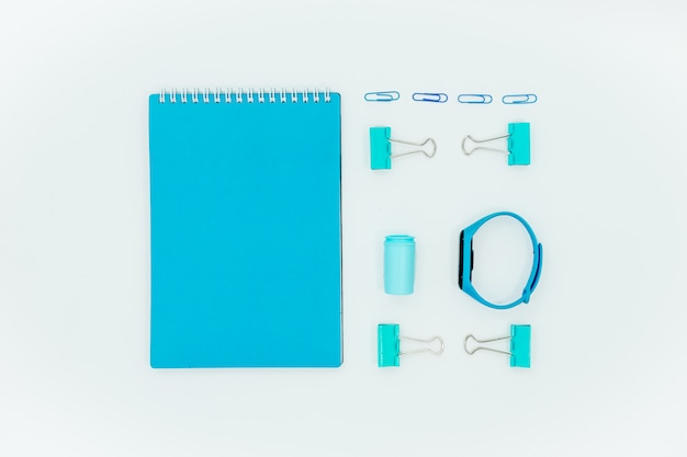 Abstract red table with stationary . blank notebook and scissors, pensils, pens. flatlay top horizontal view copyspace. Premium Photo