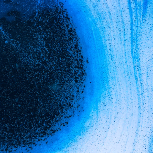 Abstract waves of foam and bubbles on blue liquid Free Photo