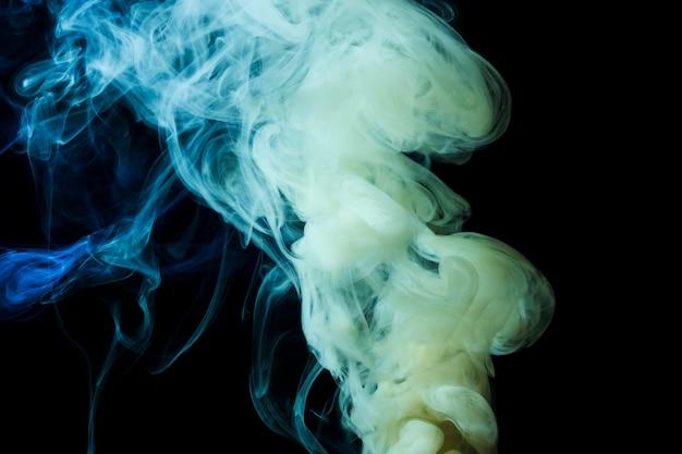 Il fumo denso bianco e blu astratto turbina su fondo nero Foto Gratuite