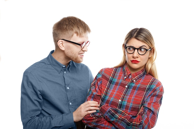 Abusive young man with stubble trying to intimidate blonde woman in checkered shirt, pulling her by sleeve. caucasian female being abused by bearded male, looking at him with eyes full of terror Free Photo
