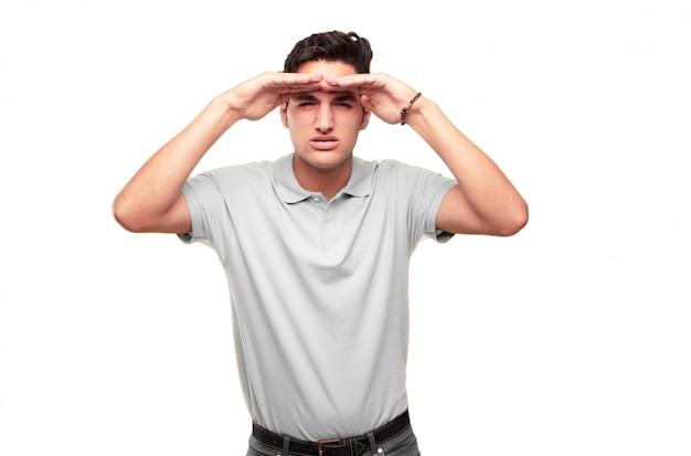Молодой красивый загорелый человек, глядя далеко вдаль, в поисках удаленного объекта с ac Premium Фотографии