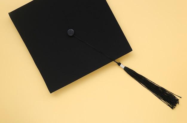 黄色の背景にアカデミックキャップ Premium写真