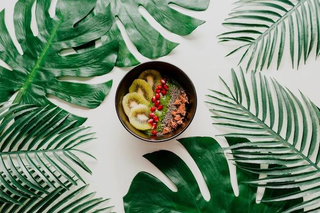 Чаша асаи со здоровыми ягодами, киви, авокадо на тропических пальмовых листах. здоровое вегетарианское питание. Бесплатные Фотографии