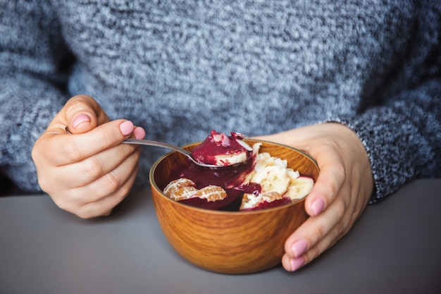Acai smoothie, granola, seeds, fresh fruits in a wooden bowl in female hands on grey table Premium Photo