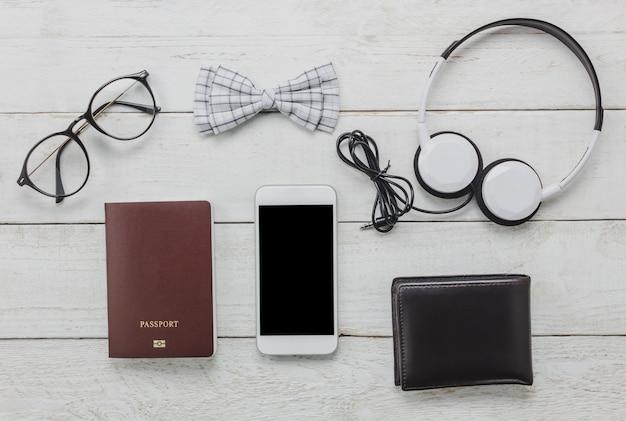 トップビューaccessoires男性服のコンセプトで旅行する。弓のネクタイ、木製の背景にパスポート。眼鏡、ヘッドホン、財布、木の木の木。 無料写真