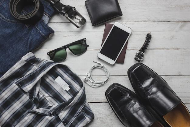 トップビューaccessoires男性服のコンセプトで旅行する。シャツ、ジーンズ、木製の背景上の携帯電話。ウォッチ、サングラス、木製テーブル上の靴。 無料写真