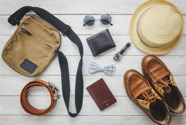 トップビューaccessoires男性服のコンセプトで旅行する。蝶ネクタイ、木製の背景にウォレット。ウォッチ、サングラス、バッグ、帽子、ベルト、木製テーブル上の靴。 無料写真