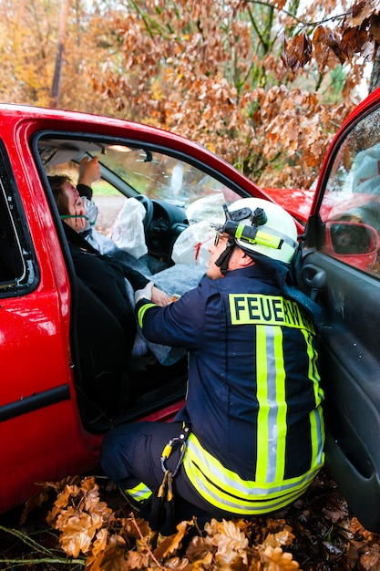 Accident, fire brigade rescues victim of a car crash Premium Photo