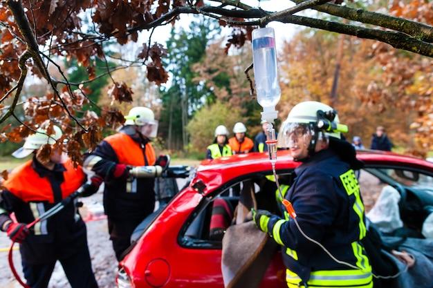 Accident - fire brigade rescues victim of a car crash Premium Photo