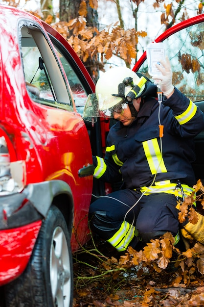 Accident, fire brigade rescues victim of a car Premium Photo