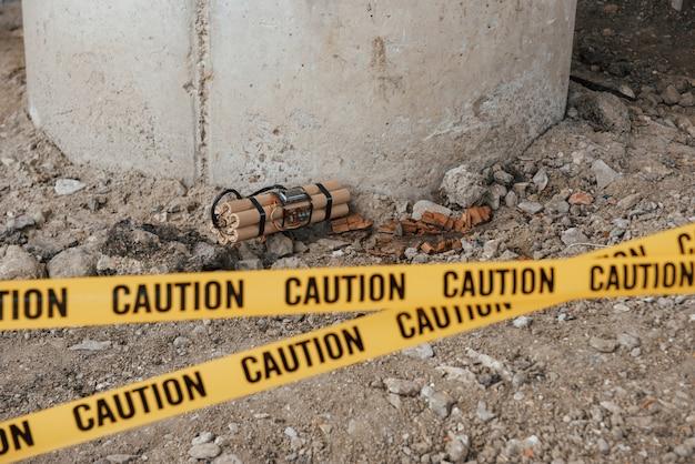 橋の下で事故。地面に横たわっている危険な爆発物。前に黄色の注意テープ 無料写真