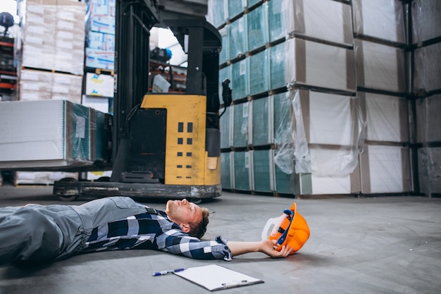 An accident at a warehouse, man on floor Free Photo