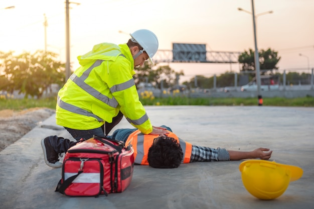 Accident at work of construction labor people, basic first aid and cpr training at outdoor. Premium Photo