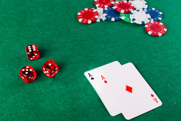 Ace playing cards; dice and chips on green poker table Free Photo