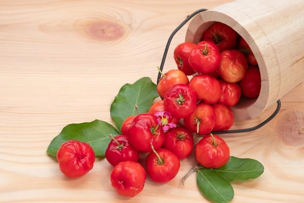 Acerola cherry in wooden bucket on wooden background. Premium Photo