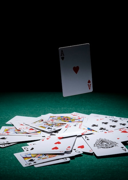 Aces card in air over the playing cards on green poker table Free Photo