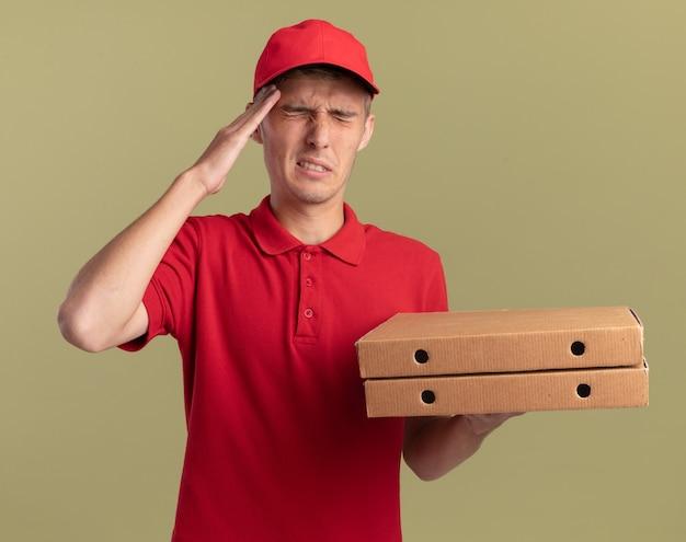 痛む若い金髪の配達の少年は額に手を置き、コピースペースでオリーブグリーンの壁に隔離されたピザの箱を保持します。 無料写真