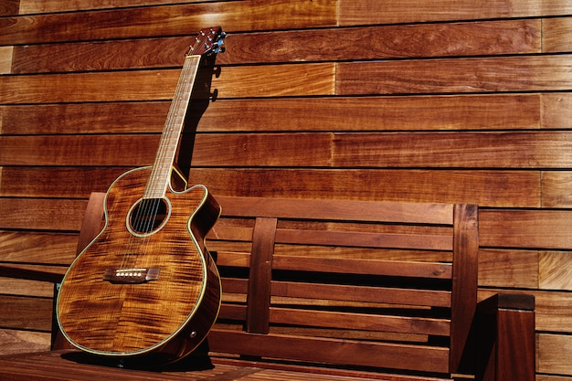 Acoustic brown guitar in wooden stripes Premium Photo
