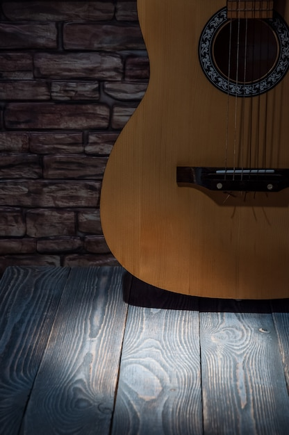 Acoustic guitar on the background of a brick wall with a beam of light on a wooden table. Premium Photo