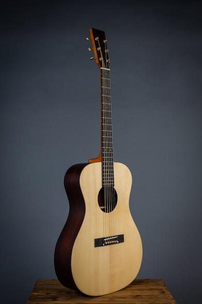 黒い壁の椅子の上のアコースティックギター。 無料写真
