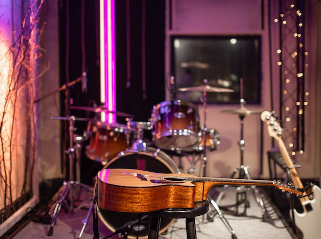Acoustic guitar on the of a recording studio. room for musicians rehearsals. Free Photo