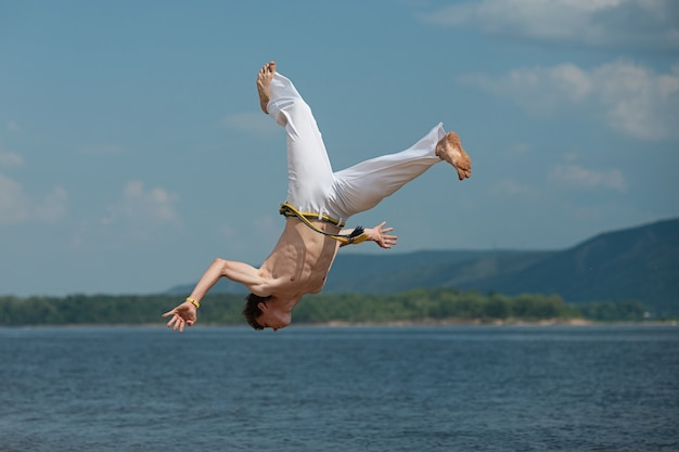 Acrobat performs an acrobatic trick, somersault on the beach. Premium Photo