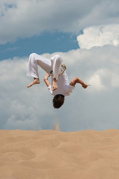 Acrobat performs an acrobatic trick, somersault on the beach. Premium Photo