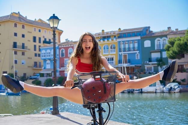 Acrobatic girl riding a bike in a marina port Premium Photo