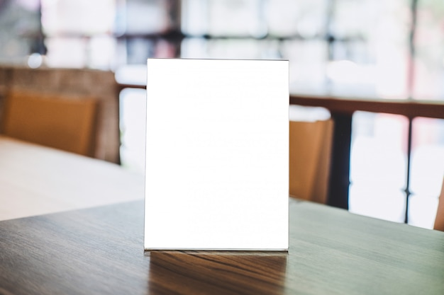 Acrylic blank frame template, blank menu frame on table in coffee shop or restaurant Premium Photo