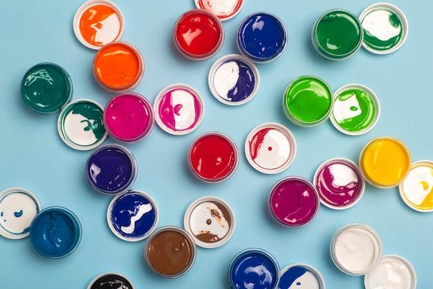 テーブルの上には、さまざまな色の絵の具が描かれています。ペンキ缶からの明るくカラフルな背景 Premium写真