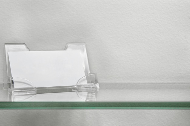 Acrylic paper stand for blank card, business card stand on glass shelf isolated Premium Photo