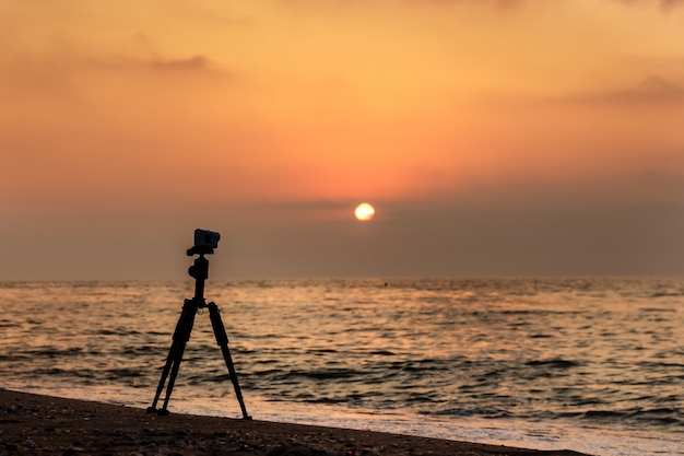 Action camera on a tripod on a sandy beach shooting a video of sunset over the sea. Premium Photo