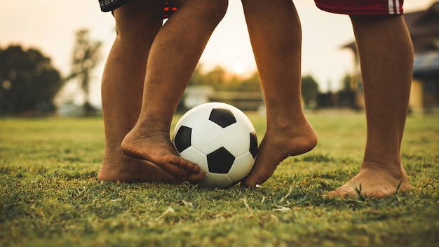 Action sport outdoors of a group of kids having fun playing soccer football. Premium Photo