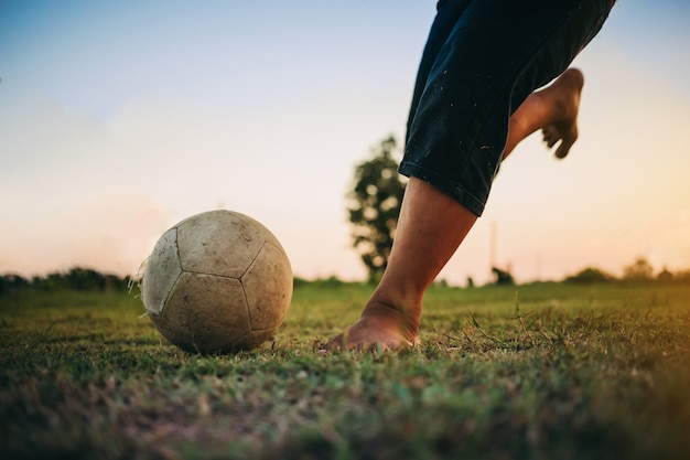 Action sport outdoors of kids having fun playing soccer football. Premium Photo
