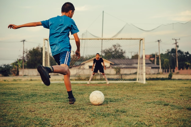 An action sport picture of a group of kids playing soccer football for exercise Premium Photo