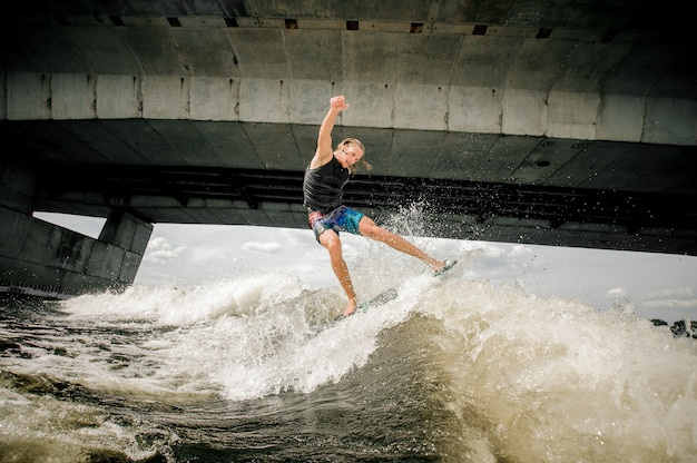 Active athletic guy wakesurfing on the board down the river against the concrete bridge Premium Photo