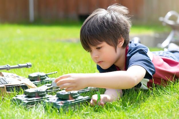Активный мальчик лежит на траве, играя с солдатами и игрушками-танками в саду Premium Фотографии