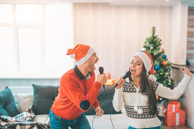 Active couple standing together and singing. they move and dance. they are concentrated on singing out loud. Premium Photo
