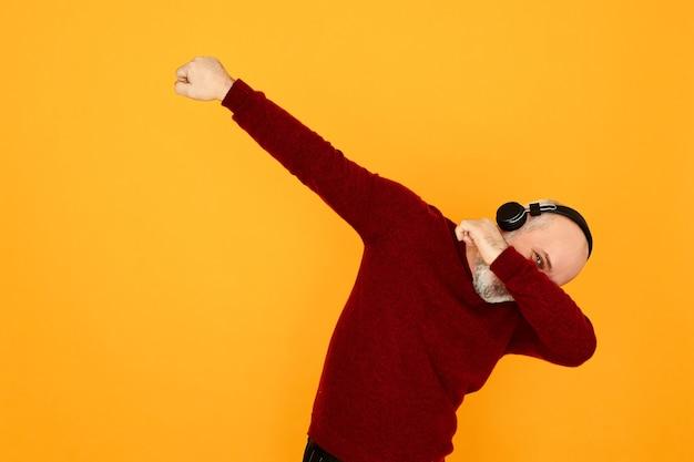 音楽を聴いているワイヤレスヘッドホンを使用して、アクティブでエネルギッシュなひげを生やした祖父。ブルートゥースのイヤフォンでラジオに合わせて踊る陽気な年配の男性、軽くたたく、ダンスを動かす、腕の下から見る 無料写真